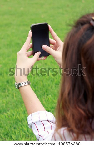 Business woman using mobile smart phone in the park - stock photo