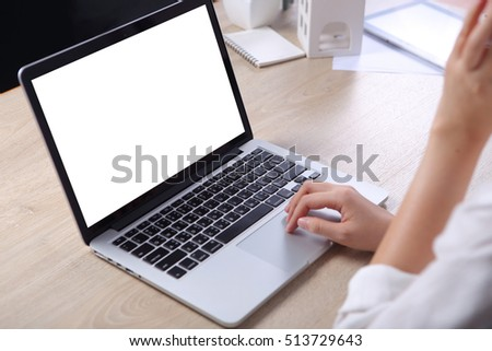 Business woman using mock up laptop on wooden desk