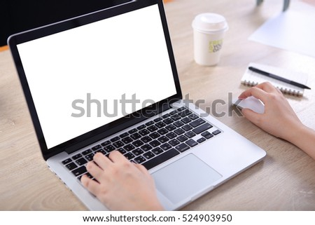Business woman using mock up laptop with note book and coffee cup on wooden desk