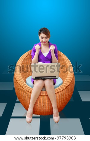 Business woman using notebook computer on the Chair