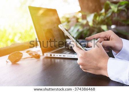 business woman using smartphone at co-working outdoor work table vintage tone in morning time. - stock photo