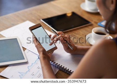 Business woman using smartphone when working with financial documents