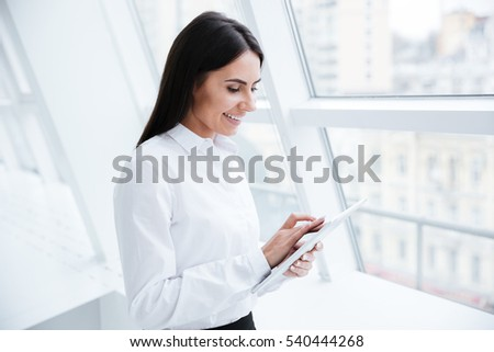 Business woman using tablet computer and standing near the window in office