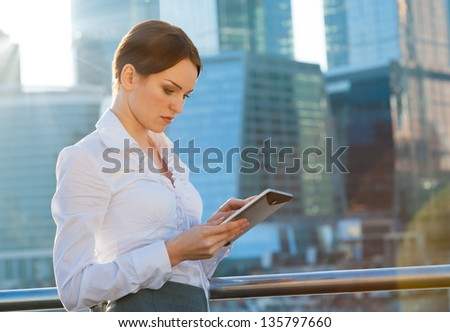 Business woman using tablet PC. Sun beams, lens flare - stock photo