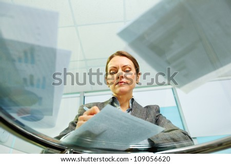Business woman viewed from below signing documents and working with papers - stock photo