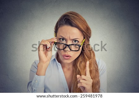 Business woman wagging her finger isolated on gray wall background - stock photo