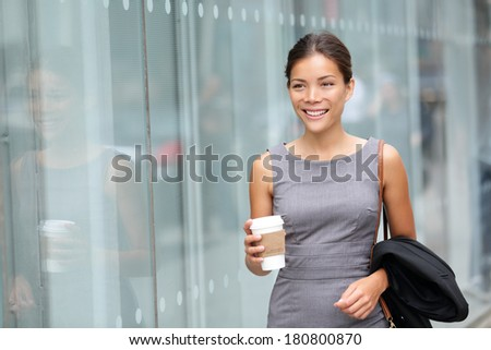 Business woman walking drinking coffee. Lawyer professional or similar walking outdoors happy holding disposable paper cup. Multiracial Asian / Caucasian businesswoman smiling happy outside. - stock photo