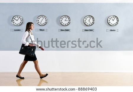 Business woman walking in a hurry past a row of clocks showing the time in various parts of the world. Business, travel, time concept - stock photo