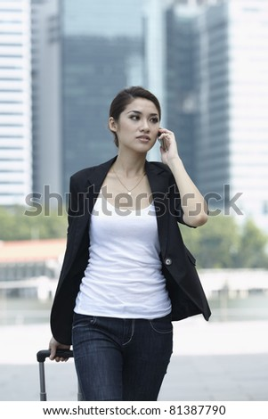 Business woman Walking with a wheeled Suitcase on phone - stock photo