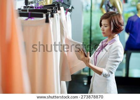Business woman with a digital tablet choosing skirt in a clothing store - stock photo
