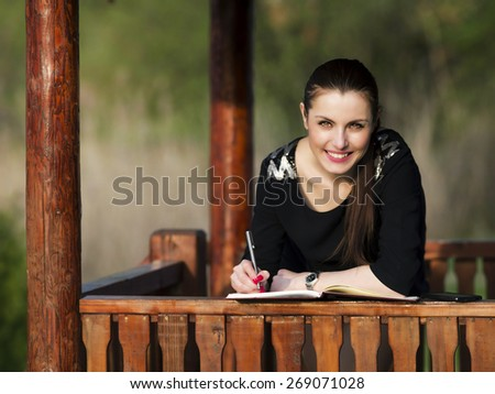 Business woman with an agenda in the park - stock photo