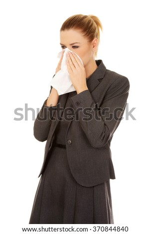 Business woman with an allergy or cold sneezing into tissue - stock photo