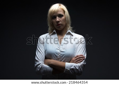 Business woman with arms crossed on black background