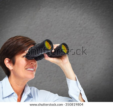Business woman with binoculars over blue background. - stock photo