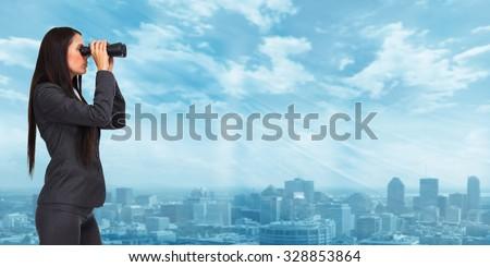 Business woman with binoculars over modern urban background. - stock photo