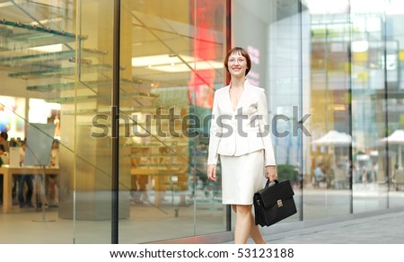 business woman with black briefcase walking street