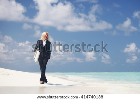 Business woman with briefcase walking on ocean beach - stock photo
