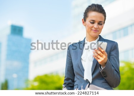 Business woman with cell phone in office district - stock photo