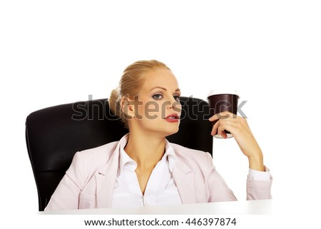 Business woman with coffee in paper cup sitting behind the desk