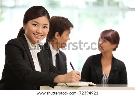 Business woman with colleagues at the back out of focus - stock photo