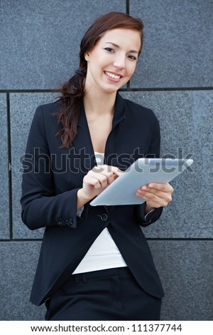 Business woman with digital tablet computer leaning on wall - stock photo