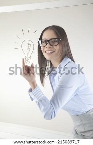 Business woman with drawn light bulb on whiteboard smiling