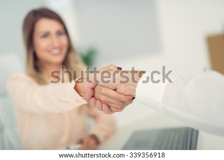 Business woman with face out of focus shakes hands with business man who can see only the hand. - stock photo