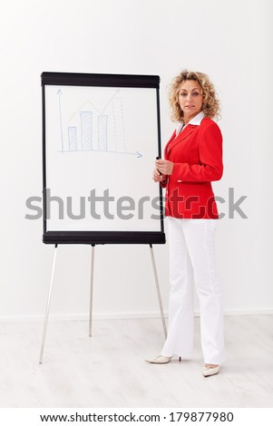 Business woman with flipchart presentation - looking confidently - stock photo