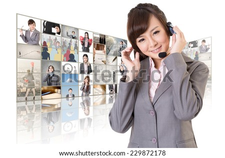 Business woman with headphone standing in front of TV screen wall. - stock photo