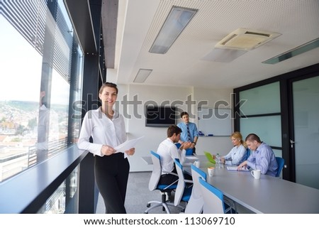 business woman  with her staff,  people group in background at modern bright office indoors - stock photo
