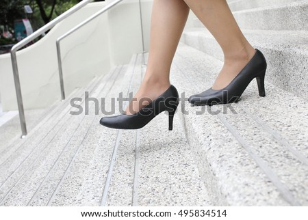 business woman with high heel shoes walking down  the stairs