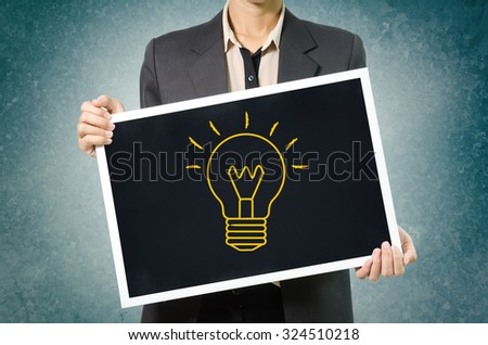 Business woman with idea light bulb icon in Black chalkboard on green wal Background. - stock photo