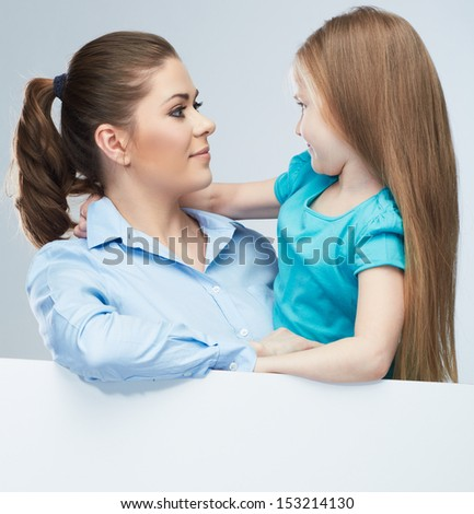 Business woman with kid girl isolated portrait behind white board. Mother and daughter embrace. Female model.