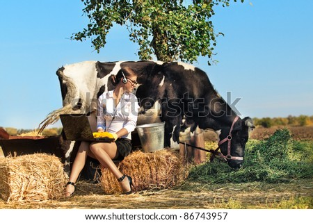 Business woman with laptop milking cow on farm - stock photo