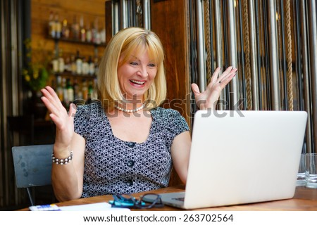 Business woman with laptop, Old senior woman with smile and surprised emotion on face, looking to computer laptop sitting in summer cafe - stock photo