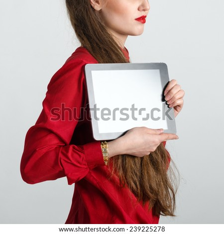 Business woman with long hair dressed in red holding and shows touch screen tablet pc with blank screen. - stock photo