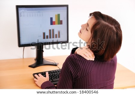 Business woman with neck pain. Focus on hand on neck with blurred monitor on table in background. - stock photo