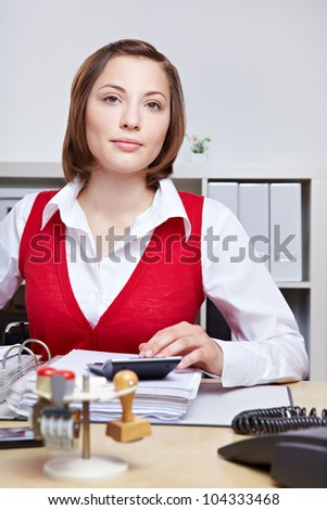 Business woman with serious look sitting at her desk in the office working - stock photo