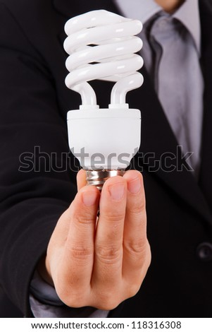 Business woman with smart suit holding and showing white economic light bulb - stock photo