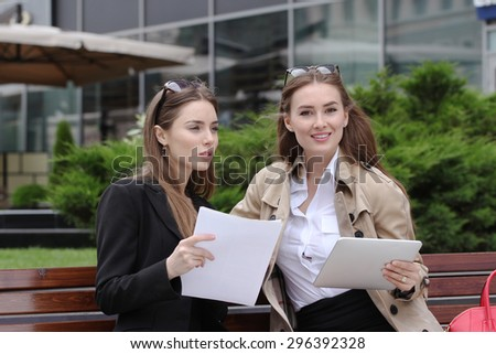 Business woman with tablet computer and documents outdoors - stock photo