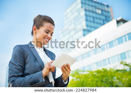 Business woman with tablet pc in office district - stock photo