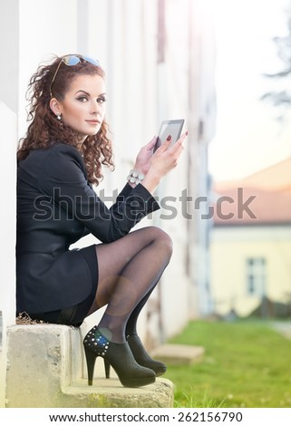 Business woman with tablet pc outdoor posing. Lens flare - stock photo