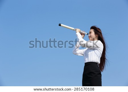Business woman with telescope ( spyglass ) looking forward Prospects for future business with blue sky background, asian beauty - stock photo