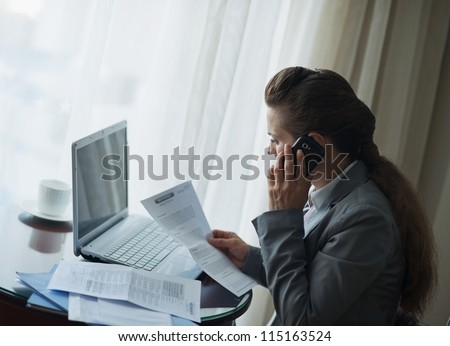 Business woman working and speaking mobile at hotel room - stock photo