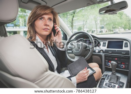 Business woman working in a car and talking on the mobile phone