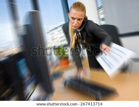 business woman working on computer in office, zoomed for dramatic effect - stock photo
