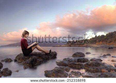 Business woman working on the beach during the holidays - stock photo