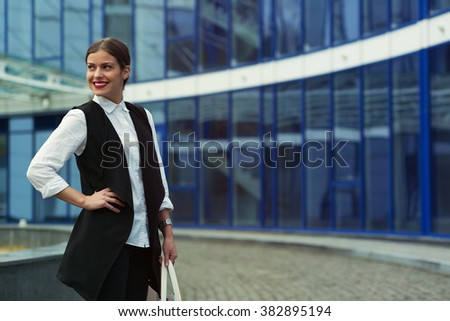 Business woman working outside in front of business center building