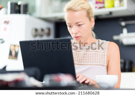 Business woman working remotly from her dining table. Home kitchen in the background. - stock photo