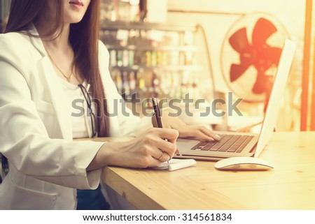 business woman working with document and laptop in office vintage tone. - stock photo